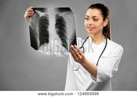 Young female doctor holding radiogram on grey background