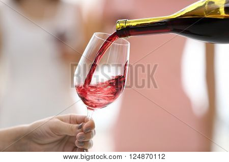 Pouring red wine from bottle into glass, close up
