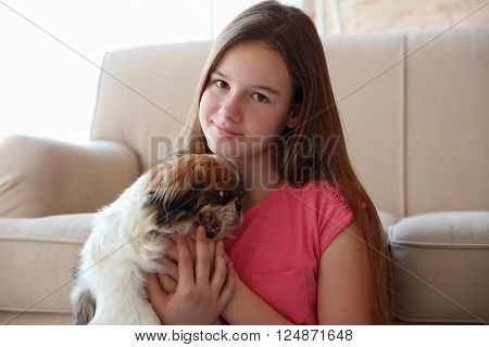 Young girl with dog on sofa indoors