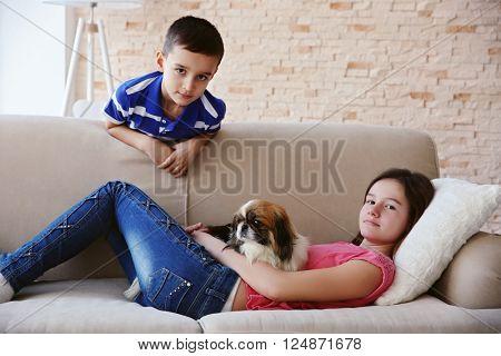 Boy and girl with dog on sofa indoors