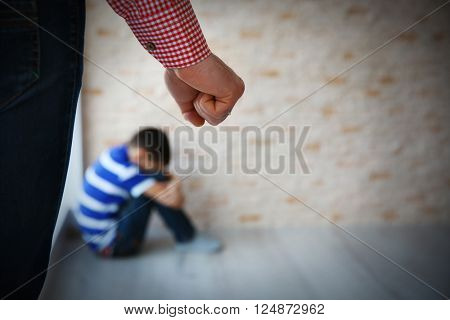 Father fist as punishment and little boy sitting on floor indoors
