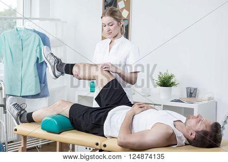 Chiropractor Exercising Man's Leg