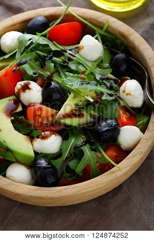 Fresh Avocado Salad With Cherry Tomatoes, Olive, Mozzarella And Arugula Closeup