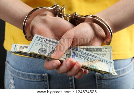 Hands in handcuffs behind back holding dollar banknotes, close up. Corruption concept