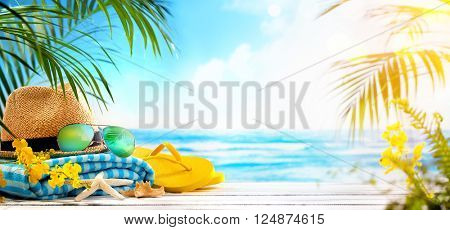 Straw hat, towel, sun glasses and flip flops on beach