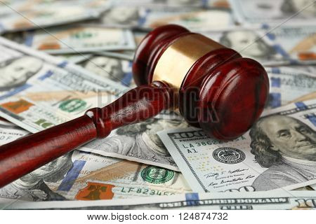 Law gavel on dollars background, closeup