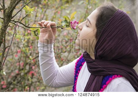 Portrait of a Beautiful Teenage Girl Outdoor in A Garden Enjoying and Smelling the Apple Tree buds.