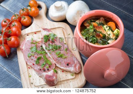 Roasted meat with vegetables in a pot and fresh pork tenderloin with herbs and spices