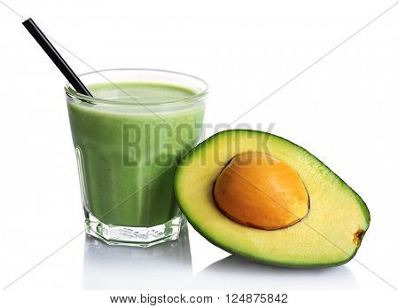 Glass of fresh avocado smoothie and avocado fruit isolated on white