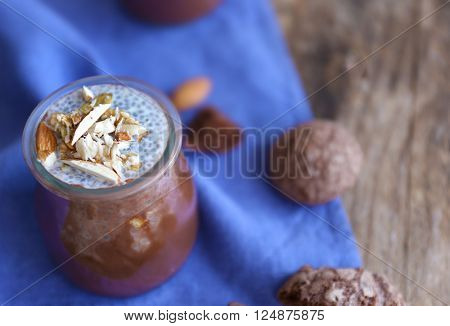 Chocolate chia seed pudding with crushed almonds on wooden table