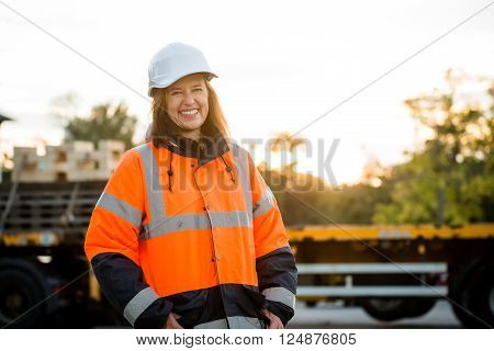 Portrait of mature woman engineer wearing protective orange jacket in work