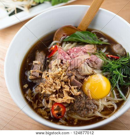 Asian beef pho noodle soup, rice noodles and vegetables. close-up. top view