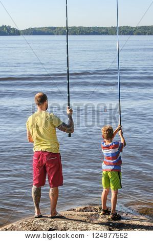Father and son lake fishing together. They're using telescopic fishing rods, fishing line, floats, and baited fishing hooks. Man has tattoos.