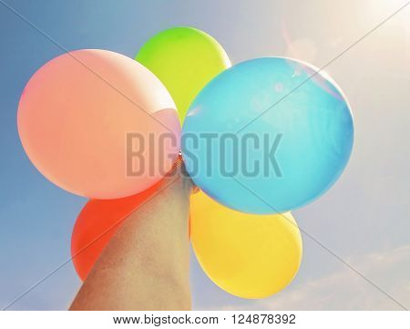 INTENTIONALLY STAGED PHOTO shot specifically into the sun of a person holding multicolored balloons up toward the sun with a lens flare toned with a retro vintage instagram filter effect app or action