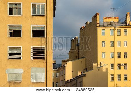 Composition of different facades of apartment buildings on the background of cloudy sky
