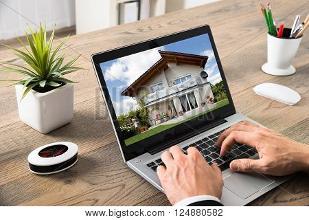 Close-up Of Businessman Looking At House On Computer At Desk In Office