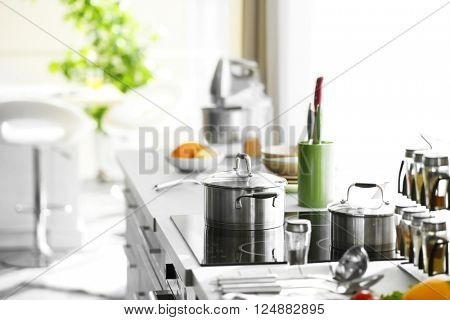Modern table and electric stove with utensils and vegetables in the kitchen beside window