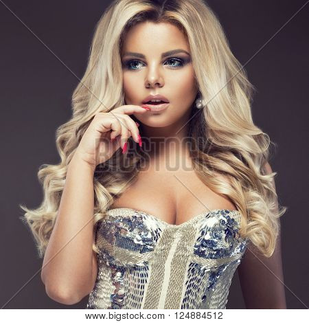 Beautiful glamor blondie woman in an elegant dress with jewels, evening makeup and curls. The beauty of the face. Photo shot in the studio.