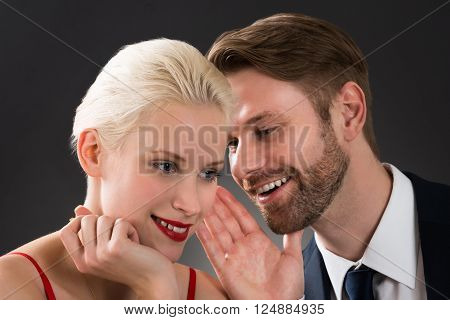 Portrait Of Young Man Whispering In Woman's Ear At A Restaurant