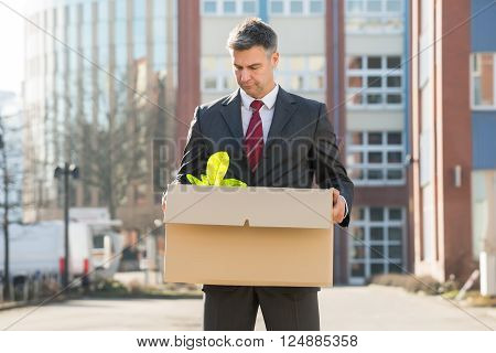 Disappointed Businessman Standing With Cardboard Box Outside Office