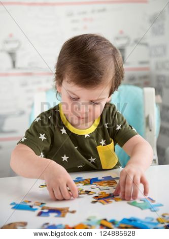 Little baby boy or toddler playing with a puzzle child development concept