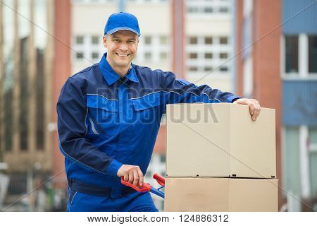 Mature Happy Deliveryman With Trolley Loaded With Cardboard Boxes Standing On Street
