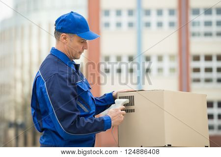 Delivery Man Standing And Scanning Cardboard Boxes With Barcode Scanner