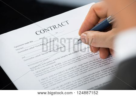 Close-up Of Businessman Hand Holding Pen Over Contract Form On Desk