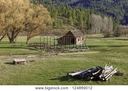 An old barn sits in a quaint little meadow next to some trees in north Idaho.