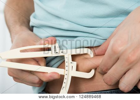 Close-up Of Man Measuring Stomach Fat With Caliper