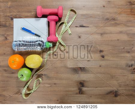 Healthy lifestyle concept.Apples lemon orange measuring tape dumbbells sport water bottle notebook and pen on wooden table