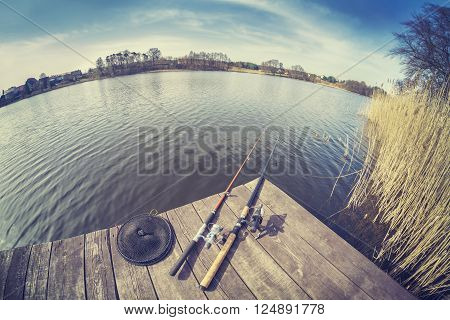 Vintage toned fisheye lens picture of two fishing rods on wooden pier.