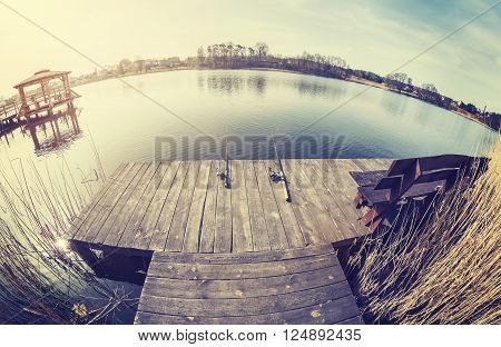 Vintage Toned Fisheye Lens Picture Of Two Fishing Rods On Wooden Pier