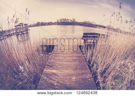 Vintage Toned Fisheye Lens Image Of A Wooden Pier On Lake.