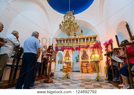 KYTHNOS, GREECE - AUGUST 14, 2014: People waiting for the Assumption liturgy to commence at the church of Panagia Stratolatissa