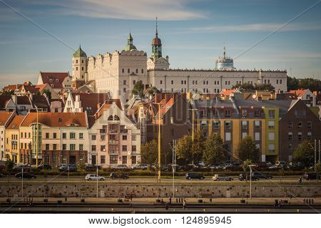 White castle with towers and green roofs and red roofs of residential and office houses and road in Szczecin, Poland