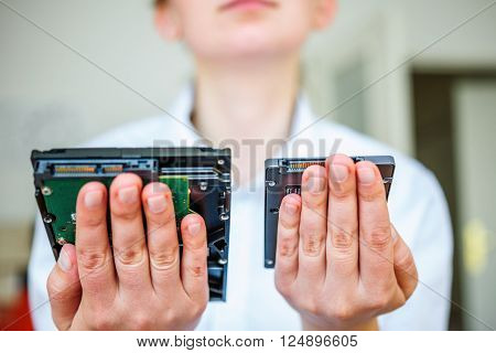IT specialist hands holding fast flash SSD - solid state drive and Hard Drive Disk HDD