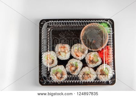 Sushi box. Japan menu in black transport box or bento box on gray background, top view, close up, from above.