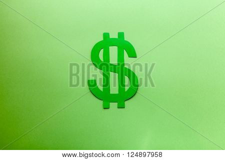 Green dollar symbol on a green background with a soft light