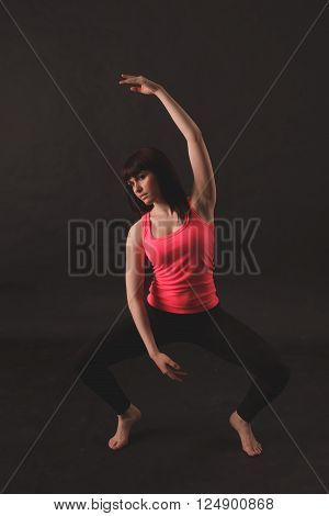 Woman doing stretching exercises over black background