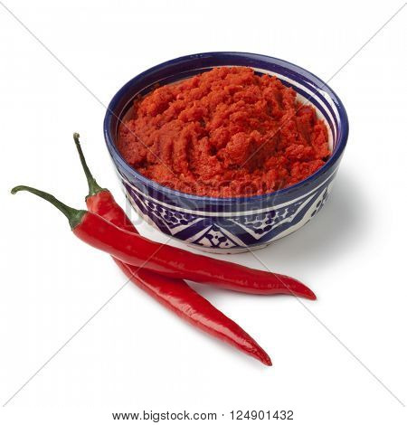 Bowl with red Moroccan harissa and fresh red chili peppers on white background