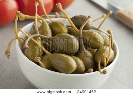 Bowl with pickled caperberries close up