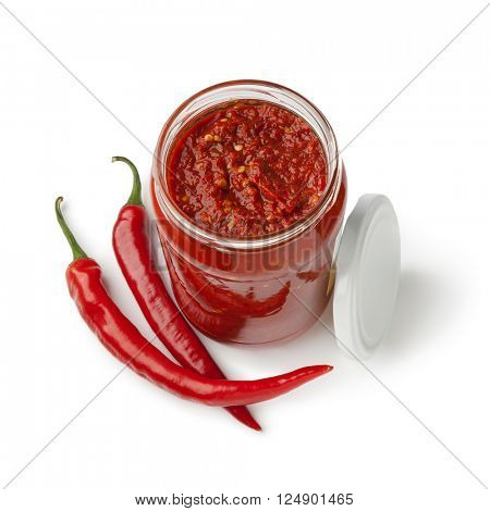 Glass jar with traditional Indonesian Sambal and fresh red chili peppers on white background