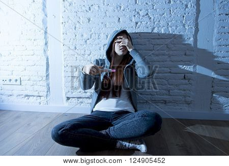 young red hair teenager girl or young woman in a hood  worried in shock and overwhelmed after positive pregnancy test devastated and depressed in unwanted maternity concept