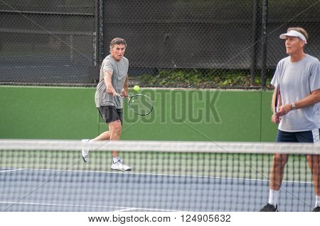 Tall Baby Boomer returning serve hit to his backhand.