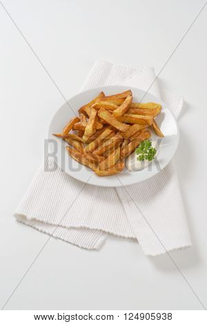 plate of crispy french fries with mayonnaise on white place mat