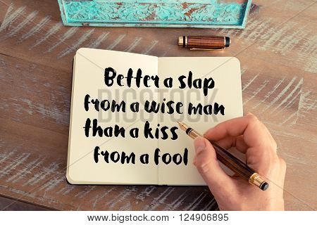 Retro effect and toned image of a woman hand writing on a notebook. Handwritten quote Better a slap from a wise man than a kiss from a fool as inspirational concept image