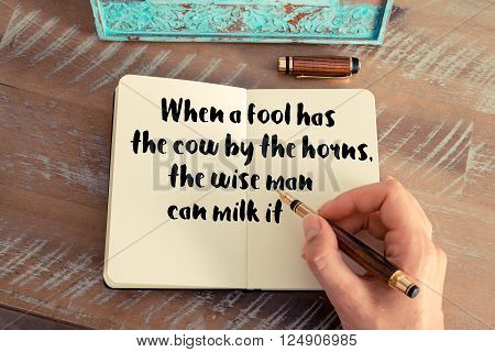 Retro effect and toned image of a woman hand writing on a notebook. Handwritten quote When a fool has the cow by the horns, the wise man can milk it as inspirational concept image