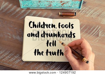 Retro effect and toned image of a woman hand writing on a notebook. Handwritten quote Children, fools and drunkards tell the truth as inspirational concept image