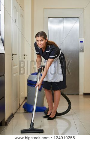 Cleaning lady in hotel corridor with vacuum cleaner during housekeeping